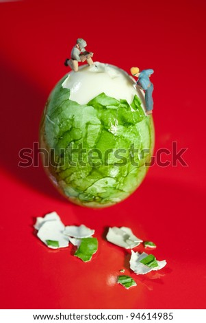 Two miniature workmen figurines peeling a hard boiled egg using power tools, macro on red background. - stock photo