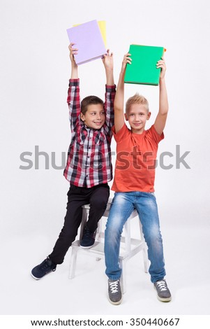 Two mischievous cheerful student with books in hand on white background laughing hands up.