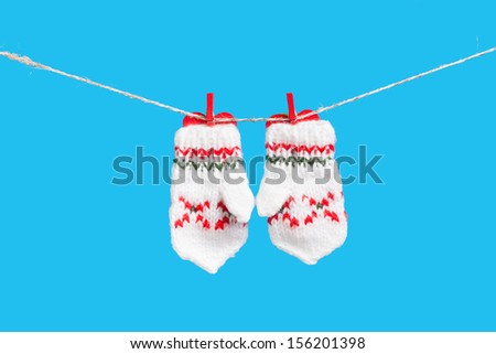 Two mittens and heart on clothesline with clothespins, isolated on blue background