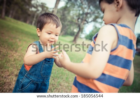 Two mixed race Asian Caucasian brothers. The older 4 year old brother teaching the younger 18 month old baby to take his first steps - stock photo