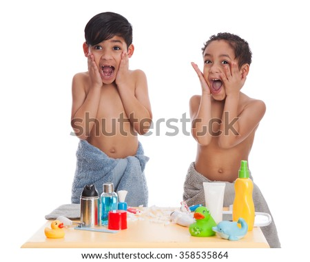 Two mixed race brothers pretending to apply aftershave.  Isolated on white. - stock photo