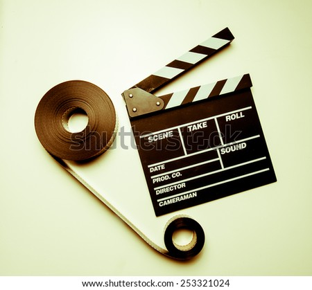 Two 35mm movie reels connected and clapperboard on right side in vintage color effect - stock photo