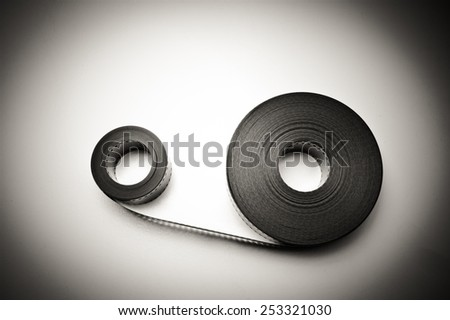 Two 35mm movie reels horizontal connected in vintage black and white with light effect - stock photo