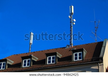 Two mobile antennas on a house roof