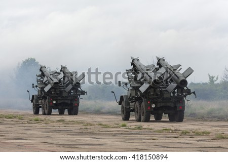 Two mobile antiaircraft missile complexes on trucks, ballistic launcher with missiles ready to attack on military powerful all-terrain transportation. Modern army industry equipment. - stock photo