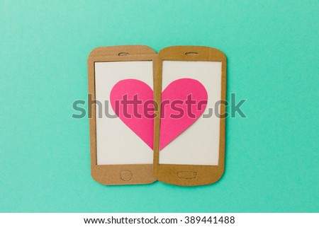 Two mobile phone screens combining a pink heart - paper illustration image concept for online dating, flirting, chatting with space available for copy text - stock photo