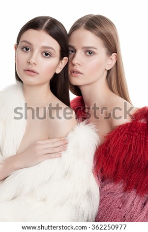 two models in fur coats posing isolated on white background