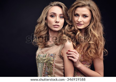 Two models with hairstyle posing in beautiful dresses