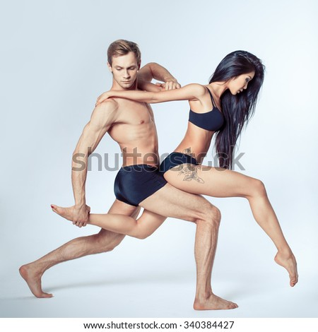 two modern ballet dancers posing on white