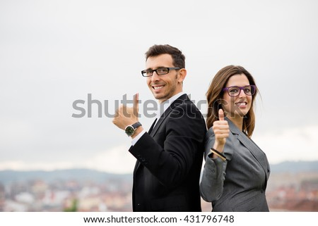 Two modern entrepreneurs partners doing thumbs up gesture for celebrating business success. Successful modern businesspeople outside. Positive elegant man and woman smiling and looking at camera. - stock photo