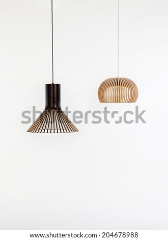 two modern wooden chandeliers on white backgrounds - stock photo
