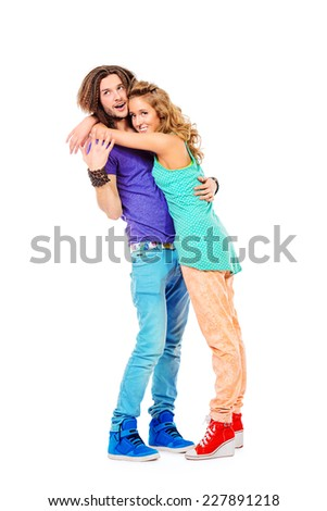 Two modern young people standing together, embracing and smiling. Full length. Isolated over white. - stock photo