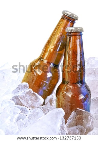 Two moist beer glass bottles are isolated on a white background with ice cubes around them for a party or bar concept.