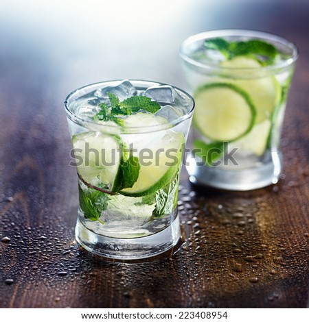 two mojito cocktails on wet wooden table - stock photo