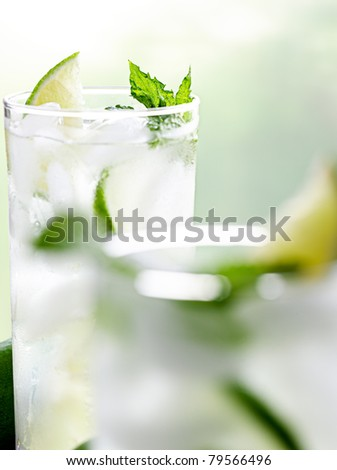 two mojitos closeup with selective focus on back glass - stock photo