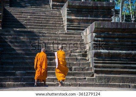 Two monks walking on stone stair in historical castle park - stock photo