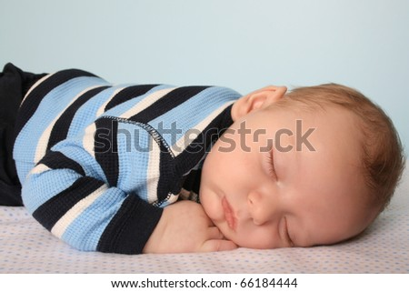 Two month old baby boy on a dotted blanket - stock photo