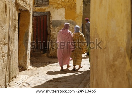 Two Moroccan women in djellabas are walking in Fes's medina (old town)