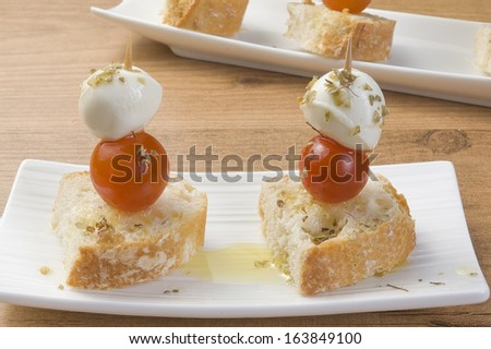two morsel of mozzarella with tomato - stock photo