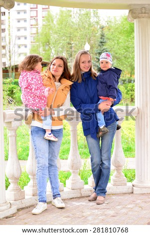 Two mothers with children on the walk in the gazebo