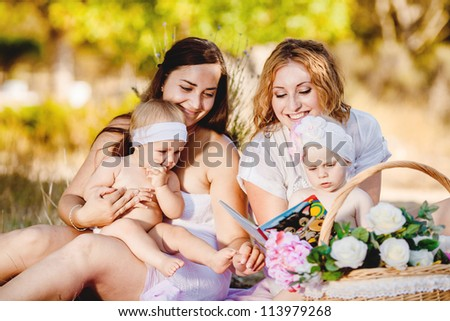 Two mothers with their children outdoor in summer park - stock photo