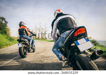 Two motorbikes driving in the nature - Friends driving racing motorcycles with their girlfriends - Three friends riding sport bikes on a week-end tour