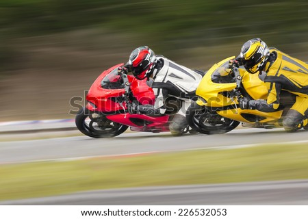 Two Motorcycles Practice Leaning Into A Fast Corner On Track