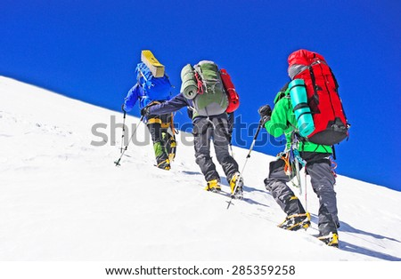 Two mountain backpackers walking on snow - stock photo