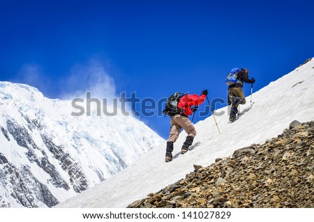 Two mountain backpackers walking on snow with peaks background, Himalayas