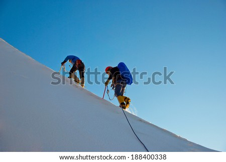 Two mountain backpackers walking on snow with peaks background, Himalayas - stock photo