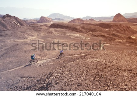 two mountain bikers in the desert - stock photo