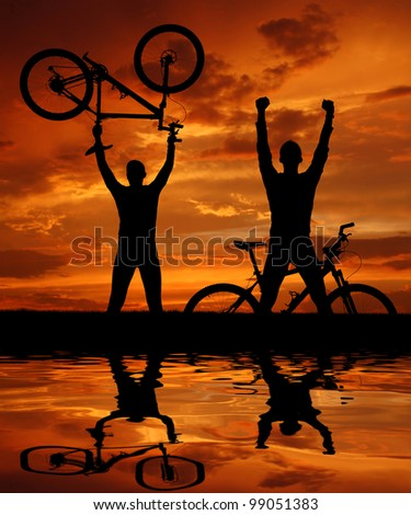 two mountain bikers silhouette in sunset