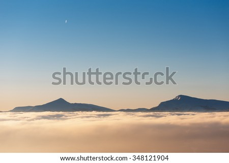 Two mountain peaks in clouds. Sunny morning. Winter landscape. Mountain Goverla and Petros, Carpathian, Ukraine, Europe - stock photo