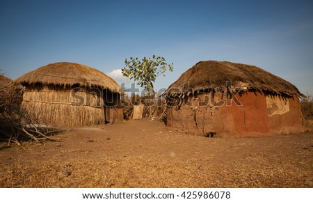 Two mud huts in masai Mara village - stock photo