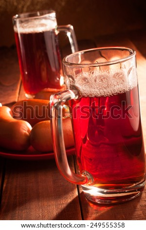 Two mugs filled with beer and hot sausages on a plate on wooden table