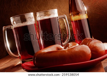 Two mugs filled with beer and hot sausages on a plate on wooden table - stock photo