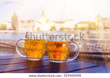 Two mugs of beer on a table against the background of street