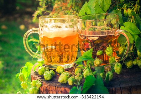 Two mugs of beer on a wooden trunk - stock photo