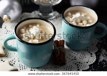 Two mugs of hot cacao with marshmallow on black table