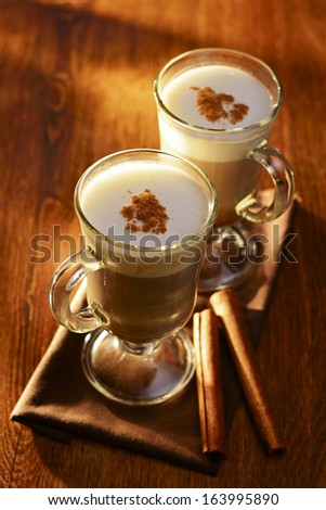 Two mugs of tasty creamy cappuccino coffee or hot chocolate topped with cinnamon powder served on a small wooden tray with cinnamon sticks for a winter treat - stock photo