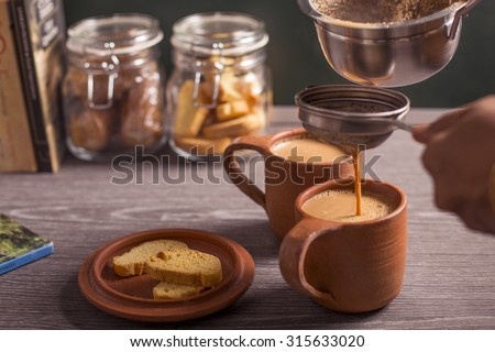 Two mugs of tea with some cookies. - stock photo