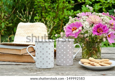 two mugs, old books, straw hat, and flowers/break/mugs