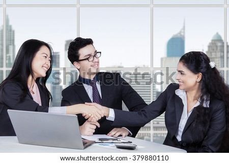 Two multi ethnic businesswomen shaking hands closing a deal in front of a businessman at workplace - stock photo