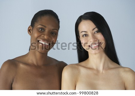 Two multi-ethnic women with bare shoulders - stock photo