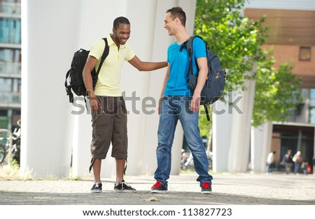 Two multicultural students laughing outdoors. Full body portrait of young African American and Caucasian students smiling.