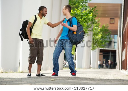 Two multicultural students walking and talking on campus. Full length portrait of an African American and Caucasian students laughing.