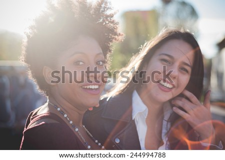 two multiethnic beautiful young woman black and caucasian having fun in town - stock photo