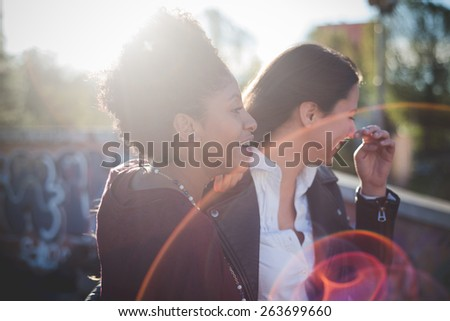 two multiethnic beautiful young woman black and caucasian having fun in town - stock photo