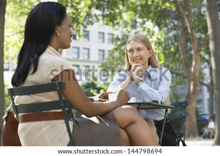 Two multiethnic female colleagues sitting at street cafe - stock photo