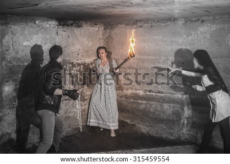 Two Murderers ready to attack their victim with a knife, torch, shaver inside a house against concrete wall Couple vampire with metal chains. Sacrifice is protected in the corner - stock photo
